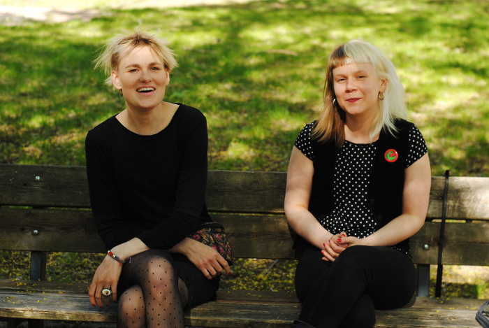 Linnea Saarits ja Vilja Joensuu istuvat puiston penkillä ja katsovat kameraan
